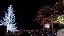 Il grande albero illuminato e lo skyline di Courmayeur colorato dai fuochi d'artificio