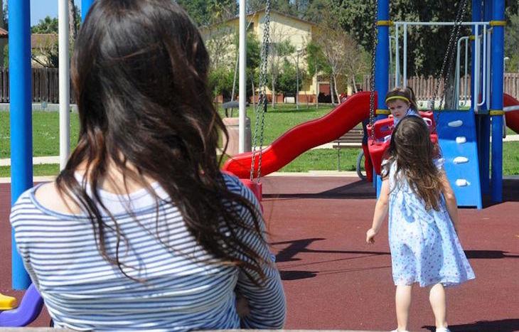 genitori e bambini parco giochi